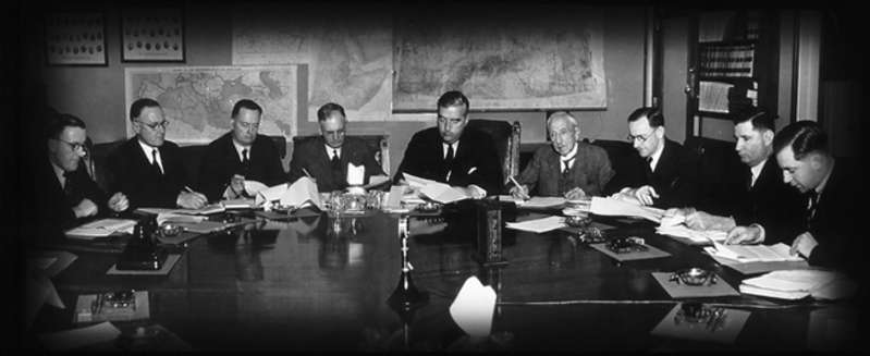 The image above shows six prime ministers in the Advisory War Council in 1940. Five of the men surrounding Prime Minister Robert Gordon Menzies (1939-41, 1949-66) once also held the title of prime minister. They are (third from left) Francis Forde (1945); (fourth from left) John Curtin (1941-45); (fourth from right) William Morris Hughes (1915-23); (second from right) Arthur Fadden (1941); and (right) Harold Holt (1966-67). Old Parliament House Collection