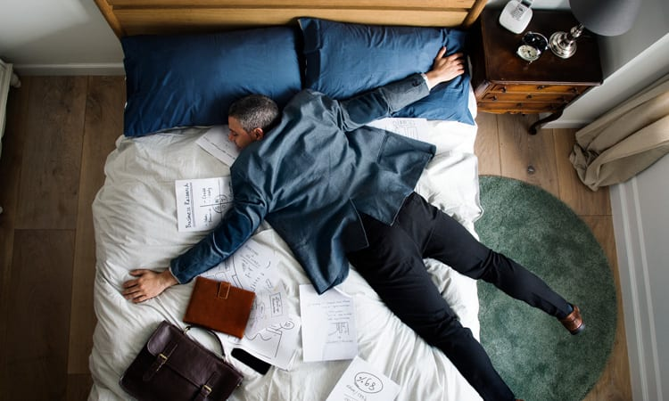 Exhausted Business Man Laying On Bed