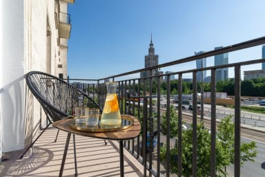 The room also has access to a balcony with a view of the city center.