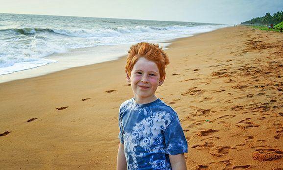 Junge auf Sandstrand lächelt in die Kamera