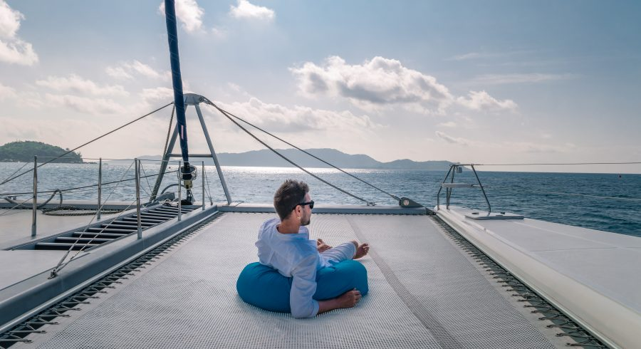 happy holiday Luxury Travel by Catamaran in the Ocean by the Seychelles island, Young man at sailing boat