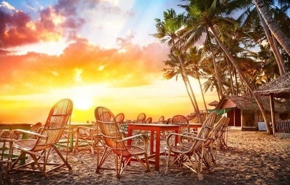 Tische und Stühle auf Sandstrand bei Sonnenuntergang in Südindien