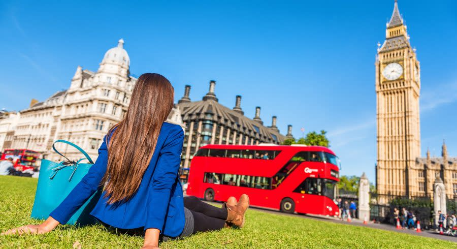 Enchanting Travels UK & Ireland Tours London city lifestyle woman relaxing in Westminster summer park, red bus and big ben tower. Urban girl outdoors.