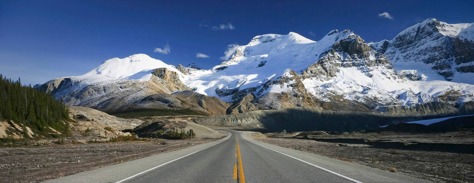 a snow covered road with a mountain in the background