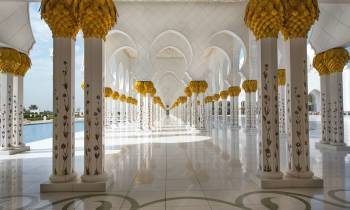 a clock hanging from the ceiling with Sheikh Zayed Mosque in the background