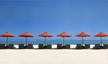 a row of beach chairs and an umbrella
