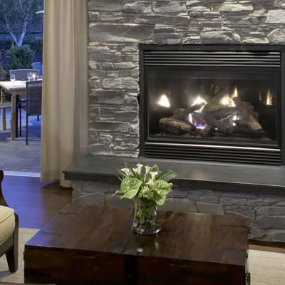 a fire place sitting in a living room filled with furniture and a fireplace