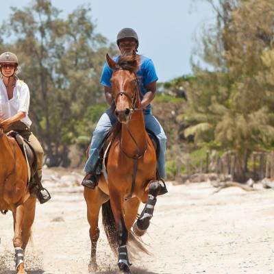 a man riding a horse on a beach