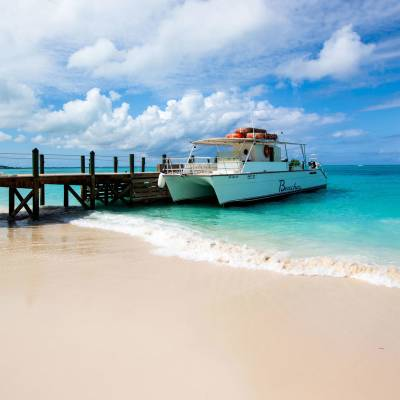 a boat sitting on top of a sandy beach next to the ocean