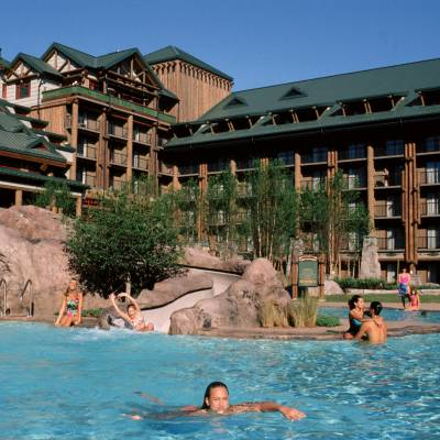 a group of people swimming in a pool of water with Disney's Wilderness Lodge in the background