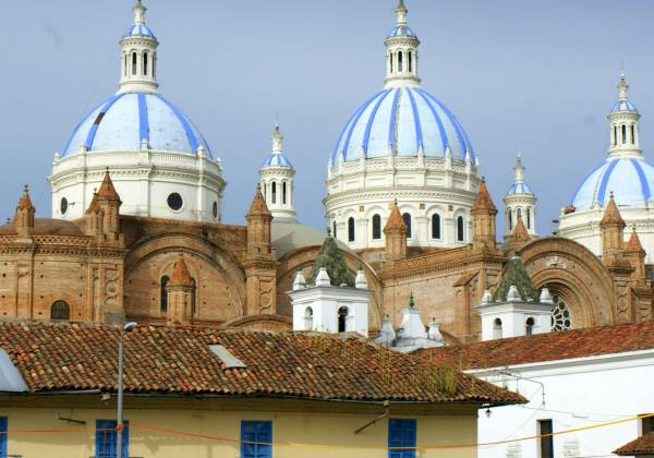 a group of people standing in front of a church with Cuenca in the background