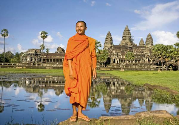 a man standing in front of a pond with Angkor Wat in the background