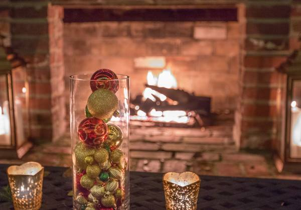 a glass of wine next to a fireplace