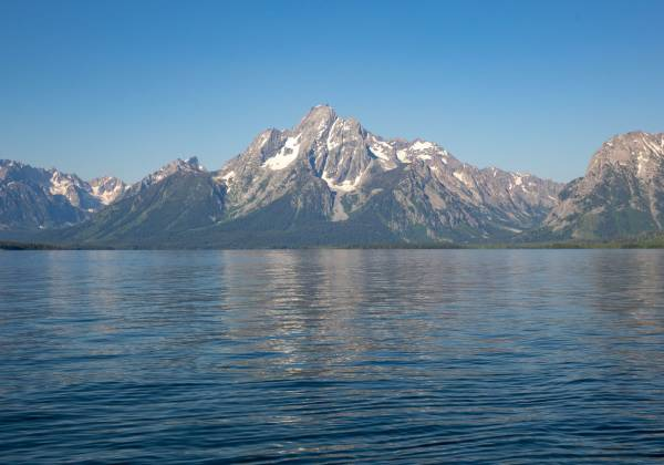a large body of water with Grand Teton National Park in the background