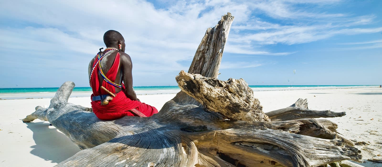 Enchanting Travels Africa Tours Maasai sitting by the ocean on the beach