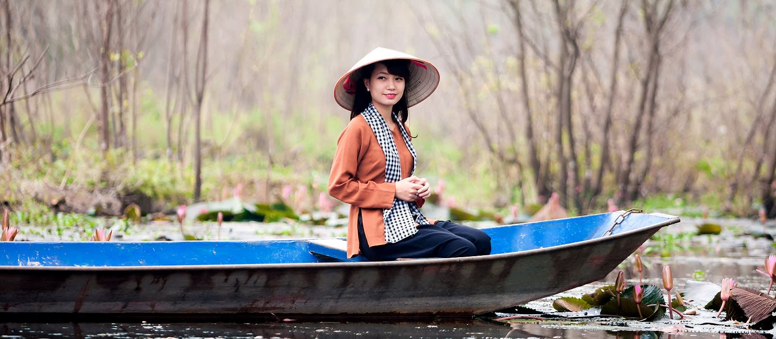 Enchanting Travels Asia Tours The girl wear traditional costume in the season of water lily at the flooded forest,