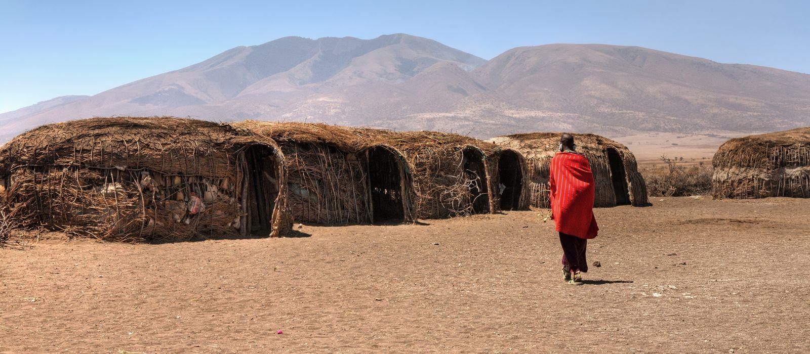 Massai-Hütten mit einer Frau in rot im Hintergrund.