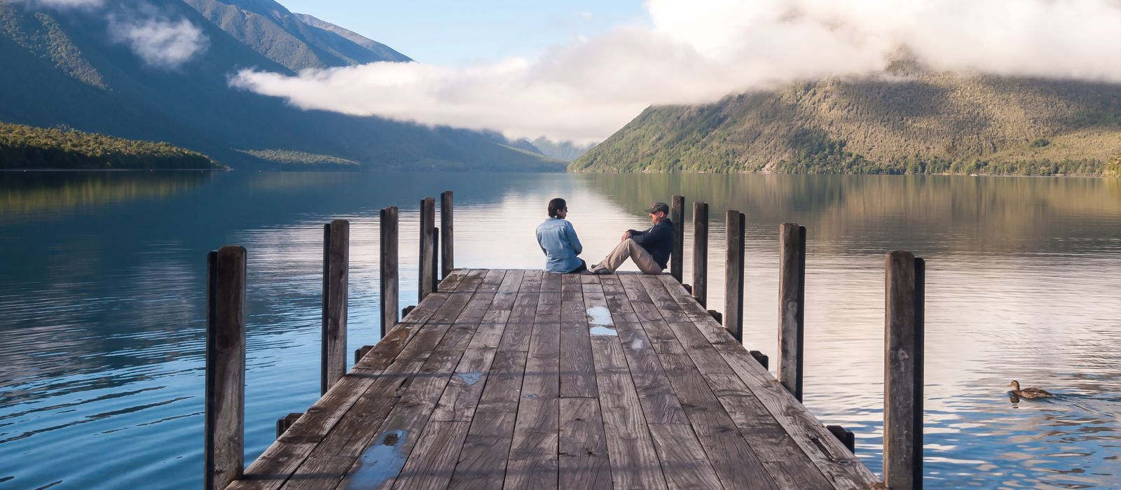 couple in love sitting on the pier at Nelson Lake National Park in the South Island of New Zealand