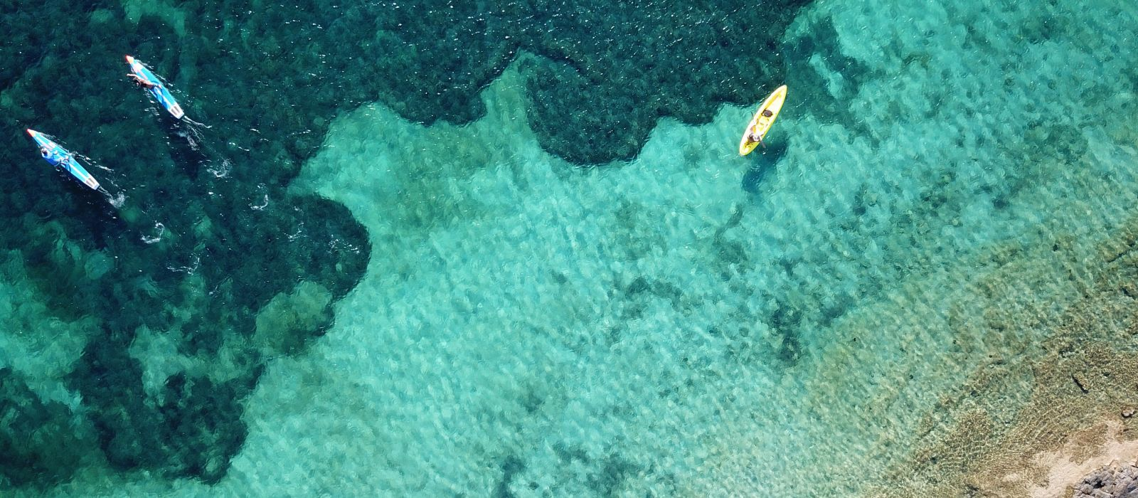 Aerial drone bird's eye view of kayaks cruising in tropical rocky seascape with turquoise and sapphire clear waters