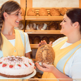 Enchanting Travels Germany Tour Sales women in bakery with cake and bread showing them to the customer