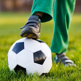 Boy stepping on a football