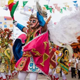 Enchanting Travels Bolivia Tours Oruro, Bolivia, carnival dancers wearing traditional masks and dresses on the street during the carnival