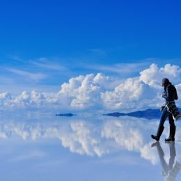 Girl on surface of salt lake Salar de Uyuni in Bolivia with sky reflection, South America