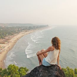 A young girl with blond hair sits on top of a mountain and looks at the sea and beach, Arambol, Goa, India