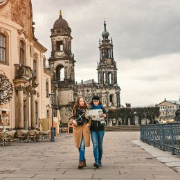 Two charming cheerful women are walking with a map along Dresden Street, Germany Tours