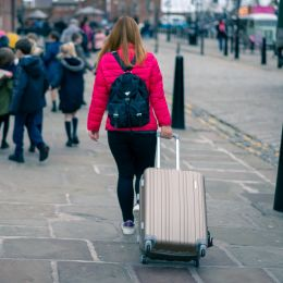Enchanting Travels UK & Ireland Tours Blurred photo,The asian girl with pink jacket walks along street carries luggage with children in background in Albert, Liverpool, England, United Kingdom