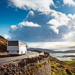 Tourist bus traveling on mountain road. Ring of Kerry, Ireland. Travel destination
