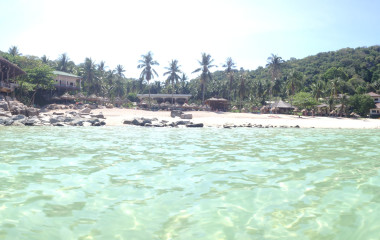 Blick vom kristallklaren Wasser zum Sandstrand mit Palmen und Lodge auf Ko Tao, Thailand