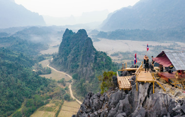 Stunning aerial view of some tourists taking pictures at the beautiful panorama from the Nam Xay viewpoint in Vang Vieng, Laos, Asia