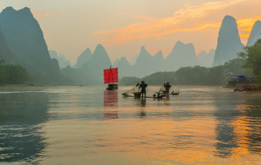Fisherman stands on traditional bamboo boats at sunrise (boat with a red sail in the background)