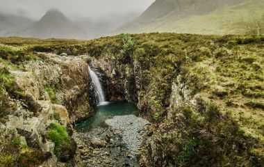 Enchanting Travels UK & Ireland Tours Waterfall in a cloudy day at the Fairy Pool trail, Isle of Skye, Scotland, UK