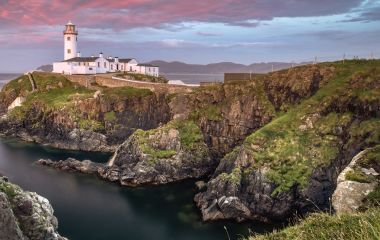 Enchanting Travels UK & Ireland Tours Donegal, Ireland. Fanad head at Donegal, Ireland with lighthouse at sunset. Colorful sky, mountains and sea
