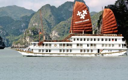 Außenansicht des weißen Kreuzfahrtschiffes Heritage Jasmine mit zwei roten Segeln vor bergiger Landschaft der Halong-Bucht, Vietnam