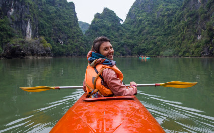 Junge Frau im Kayak in der Halong-Bucht dreht sich zur Kamera um, Vietnam