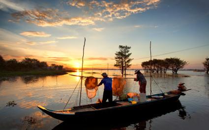 Zwei Fischer im Kanu auf dem Mekong bei Sonnenuntergang, Vietnam