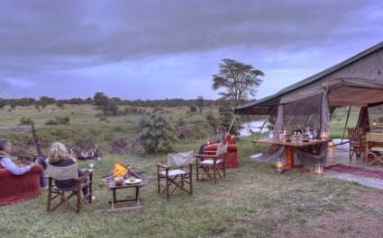 Drei Touristen sitzen gemütlich bei einem Lagerfeuer im Ol Pejeta Bush Camp im Laikipia-Reservat, Kenia