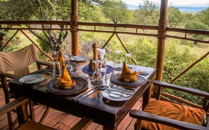Gedeckter Tisch auf der Terrasse einer Lodge mit Blick auf die Wildnis, Afrika