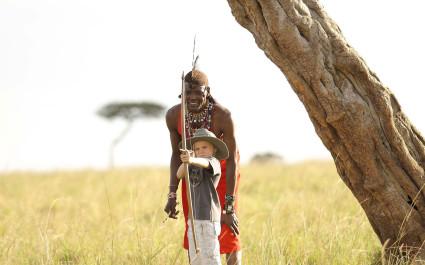 Mann in traditioneller Kleidung lehrt einem Kind das Bogenschießen, Afrika