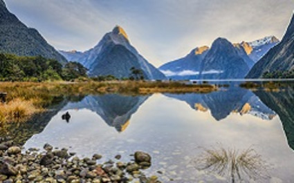 Enchanting Travels New Zealand Tours First light on Mitre Peak and surrounding mountains at Milford Sound