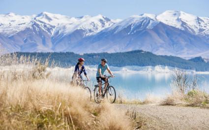 Zwei Menschen auf einem Radweg vor der Kulisse des Mount Cook, Neuseeland