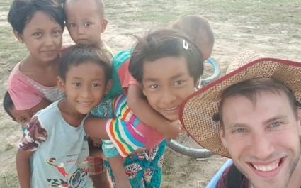 Selfie eines jungen Touristen mit einer Gruppe von Kindern in einem Dorf in Myanmar