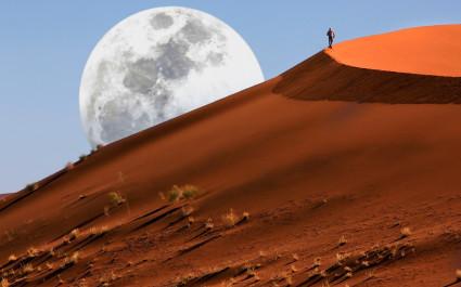Mensch wandert eine Düne des Sossusvlei in Namibia entlang
