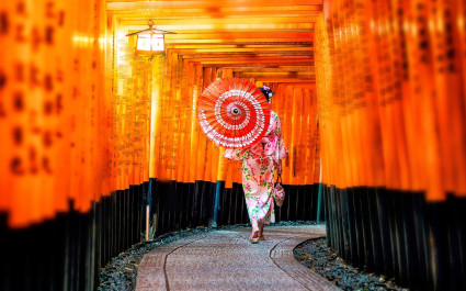 Japanese girl in Yukata with red umbrella at Fushimi Inari Shrine in Kyoto, Japan - best time to visit Japan