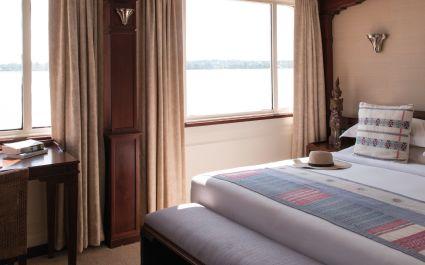Bett und Fenster mit Blick aufs Wasser