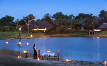 Woman standing at outside dining table of Arathusa Safari Lodge in Kruger, South Africa