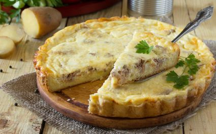 Enchanting Travels France Tours A classic quiche Lorraine pie with potatoes, meat and cheese on a wooden table - cuisine in France